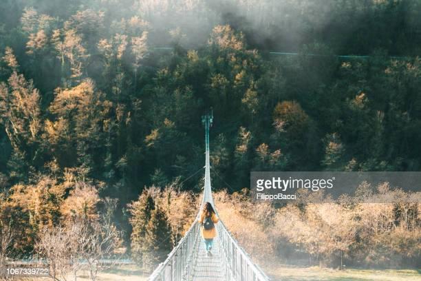 junge frau mit einer gelben jacke auf einer hängebrücke - hängebrücke stock-fotos und bilder