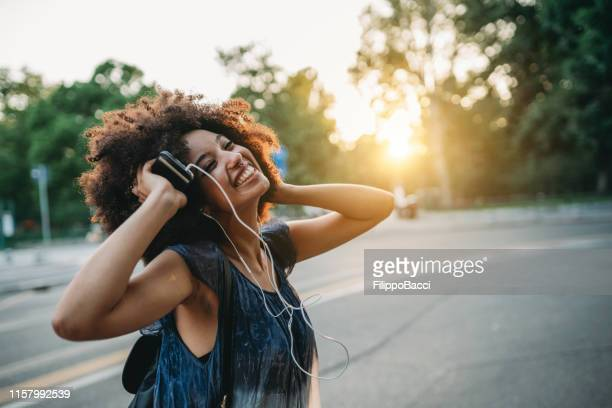 young adult woman with afro hair dancing in the city at sunset while listening to music - musica foto e immagini stock