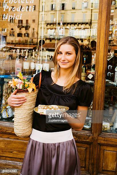 Young adult woman with flowers and sweets , Siena , Italy