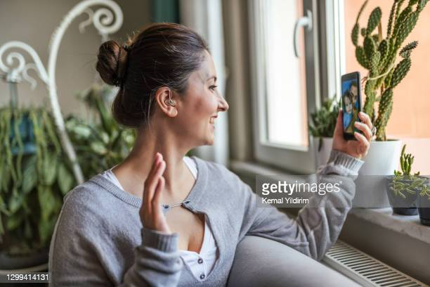 young adult woman with hearing aid having video conference. - inserting stock pictures, royalty-free photos & images