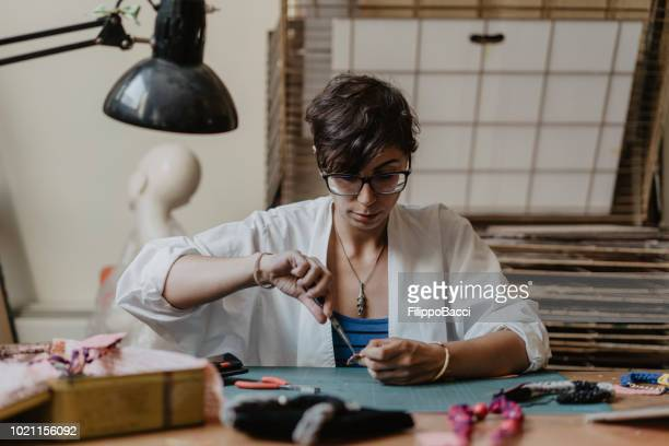 Young adult woman working on the creation of some necklaces