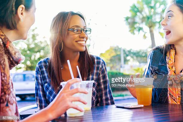 Young adult women enjoying drinks together on patio