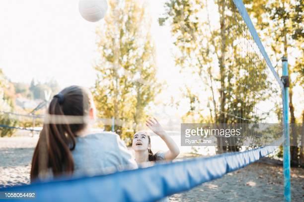 junge erwachsene frauen outdoor volleyball spielen - strandvolleyball spielerin stock-fotos und bilder