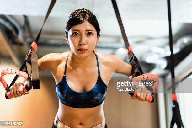 若年の成人女性で、十字のジムでワークアウトします。 - 練習 ストックフォトと画像