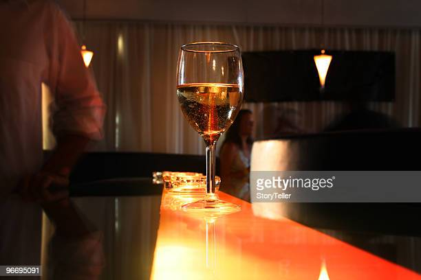 Junge Erwachsene im Club mit einem Glas Wein an der Bar