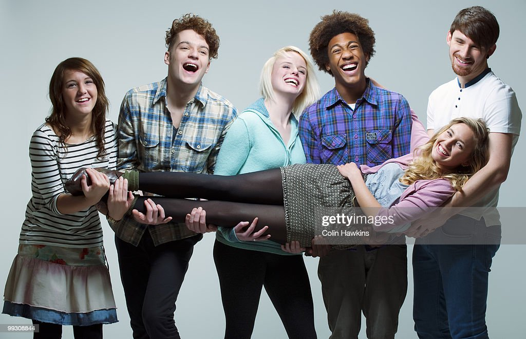 5 young adults carrying young woman : Stock Photo