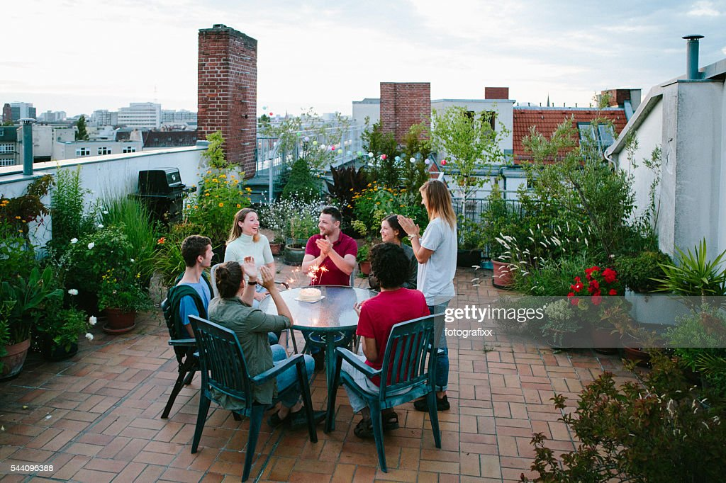 Young Adults Celebrating Birthday Roofgarden Cake With Sparklers Stock Photo