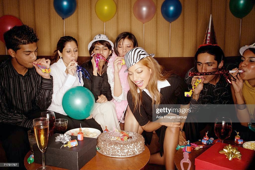 Young Adults Celebrating Birthday With Noisemakers And Party Hats Stock Foto