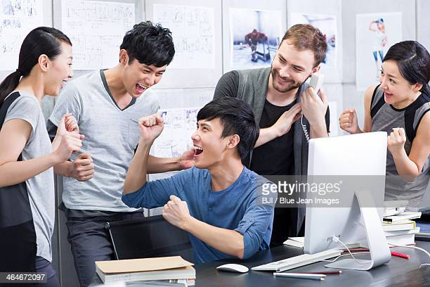 Young adults celebrating in office