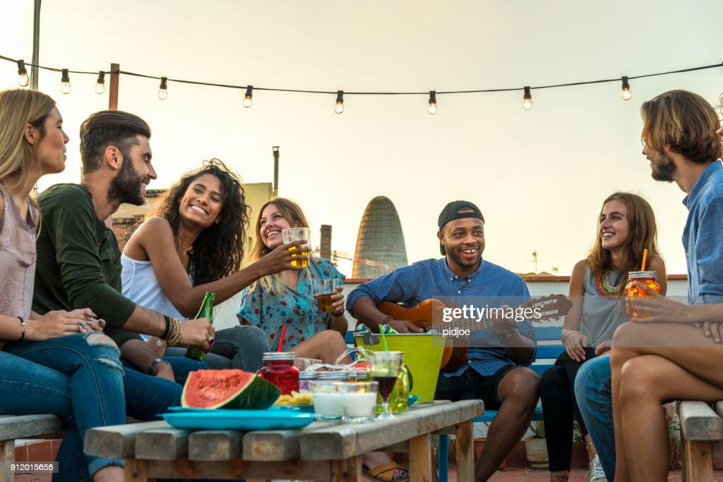 Young adults celebrating life and friendship on a rooftop in Barcelona, Spain. candid shot of eight young friends having fun on a rooftop party : Stock Photo