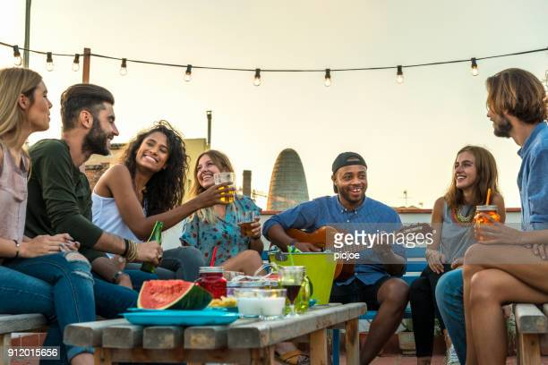 young adults celebrating life and friendship on a rooftop in barcelona, spain. candid shot of eight young friends having fun on a rooftop party - outdoor party stock pictures, royalty-free photos & images
