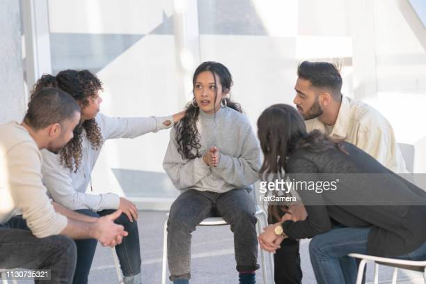 young adults consoling a friend in group therapy - enslaved stock pictures, royalty-free photos & images