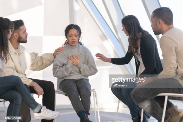 young adults consoling a friend in group therapy - vulnerability stock pictures, royalty-free photos & images