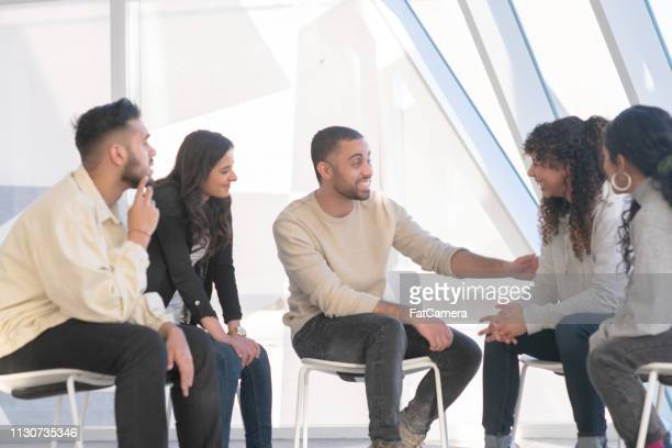 Young adults consoling a friend in group therapy