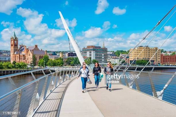 young adults cross the peace bridge in derry northern ireland uk - derry northern ireland stock pictures, royalty-free photos & images