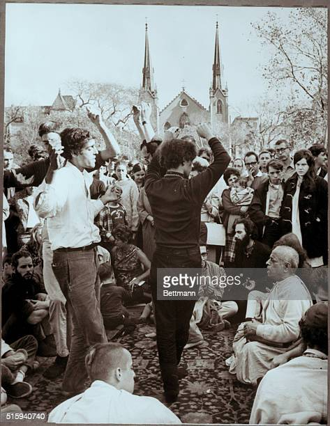 Young adults dance and sway as others clap to the chanting of Swami A.C. Bhaktivendanta in Tomkins Square Park, New York. | Location: Tomkins Square...