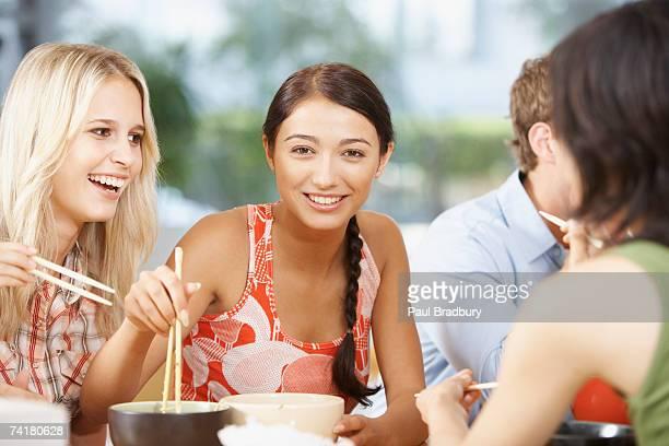 Jeunes adultes manger des bols de nouilles avec des baguettes chinoises
