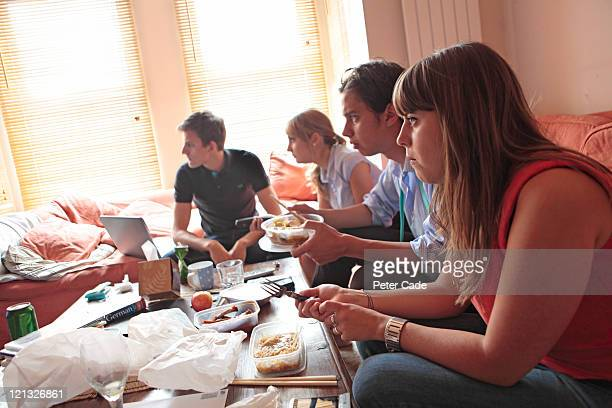 young adults eating dinner in shared house