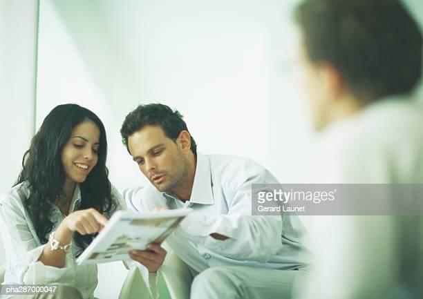 Young adults examining catalog