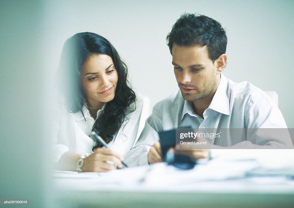 Young adults examining documents and calculating : Stockfoto
