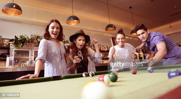 Young adults in bar, playing pool