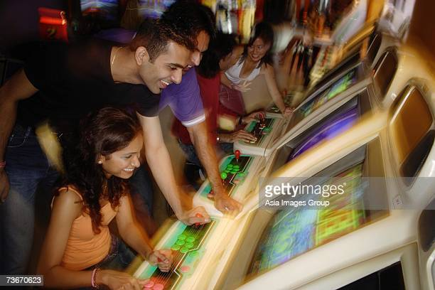 Young adults in video arcade, playing games
