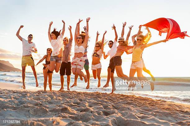 Young adults jumping in unison on the beach