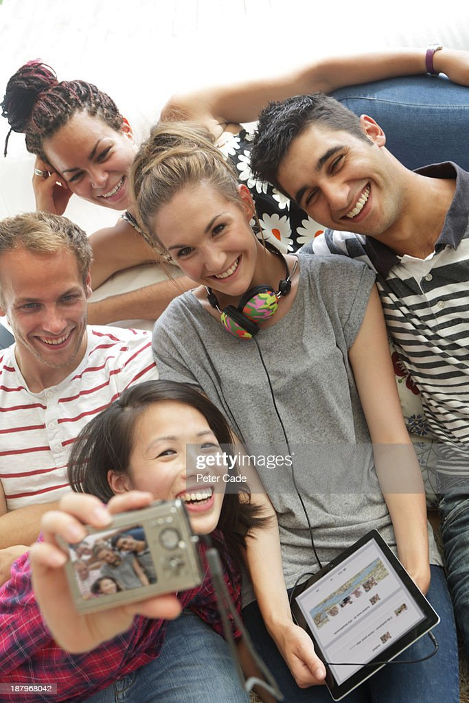 Young adults on sofa taking photo of themselves : Stock Photo
