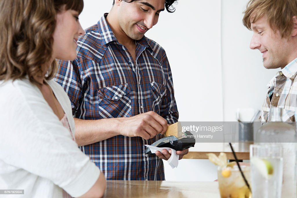 Young adults paying bill at bar : Stock Photo