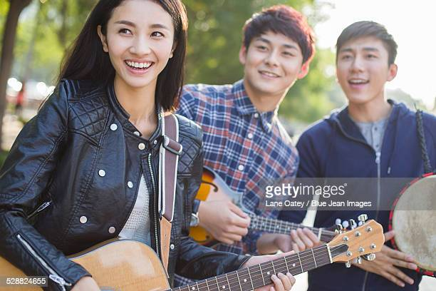 Young adults playing musical equipment on street
