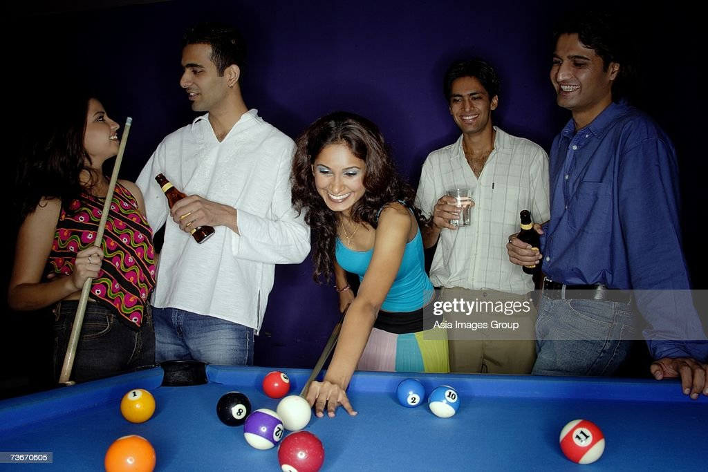 Young adults playing pool and drinking beer : Stock Photo