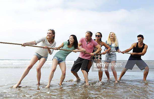 Young adults playing tug 'o' war on beach