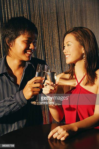 young adults raising wine glasses, looking at each other - clubkleding stockfoto's en -beelden