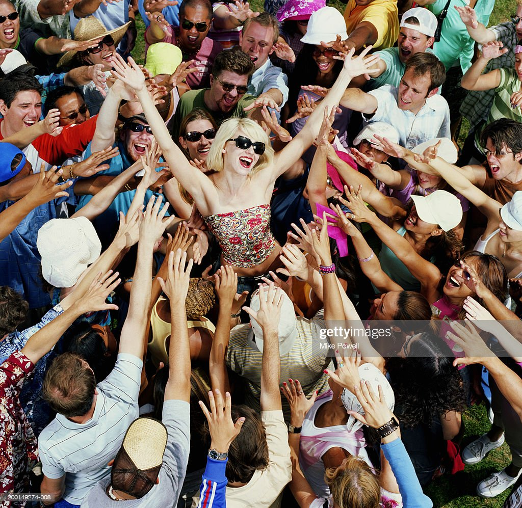 Young adults reaching for female celebrity, elevated view : Stock Photo