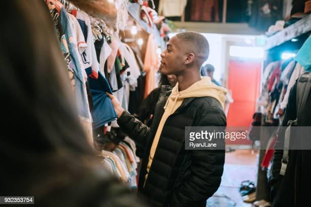 young adults shop for clothes at thrift store - ver a hora imagens e fotografias de stock