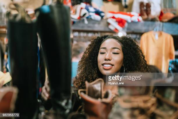 young adults shop for clothes at thrift store - black boot stock pictures, royalty-free photos & images