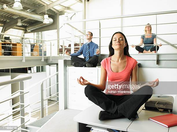 Young adults sitting on office desks in a yoga position