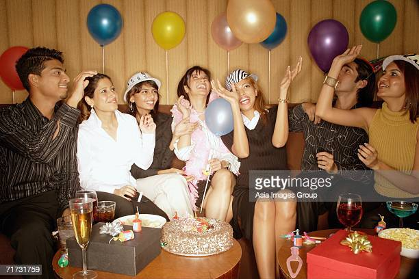 young adults sitting side by side, celebrating, playing with balloons - clubkleding stockfoto's en -beelden