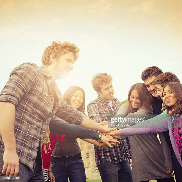 Young adults stacking hands to signify teamwork