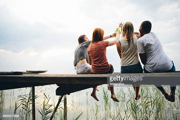 young adults toast with beer and relax on a jetty - clique stock photos and pictures