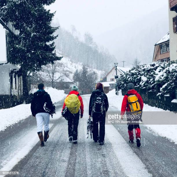 Young adults walk along snowy rural road together