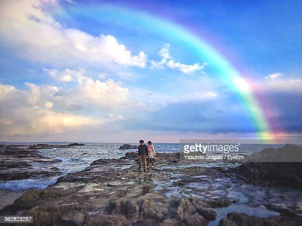 Young Adults Walking On Rocks Against Rainbow Sky