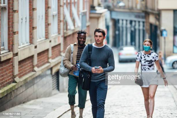 young adults walking through town - commuter stock pictures, royalty-free photos & images