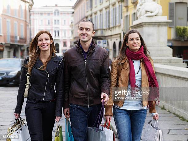 young adults walking with shopping bags - man met een groep vrouwen stockfoto's en -beelden