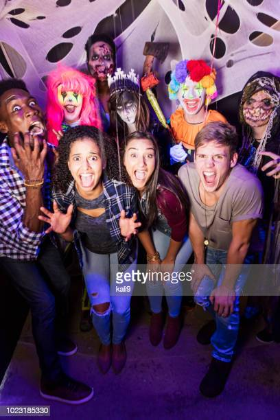 young adults with zombies and ghouls in haunted house - halloween party stock photos and pictures