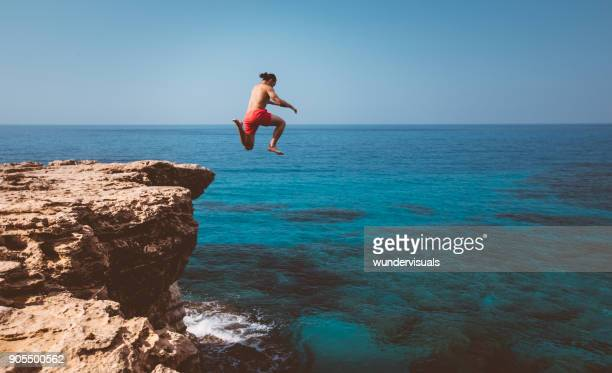 Young adventurous diver jumping off cliff into ocean