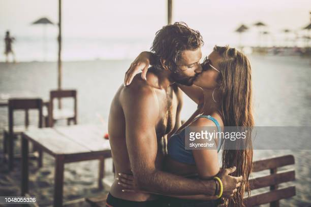 young affectionate couple kissing on the beach. - coppia passione foto e immagini stock