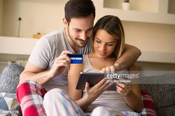 Young affectionate couple shopping online using digital tablet