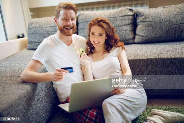 Jeune couple affectueux shopping en ligne via ordinateur portable