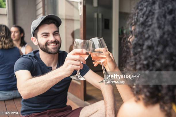Young affectionate couple toasting with wine glasses